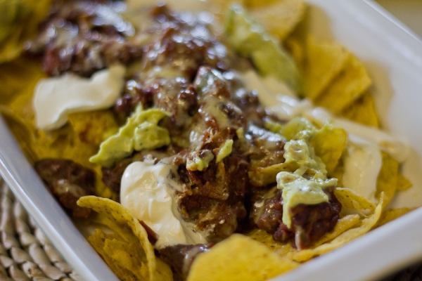 Nachos with chili, guacamole, sour cream and melted cheese
