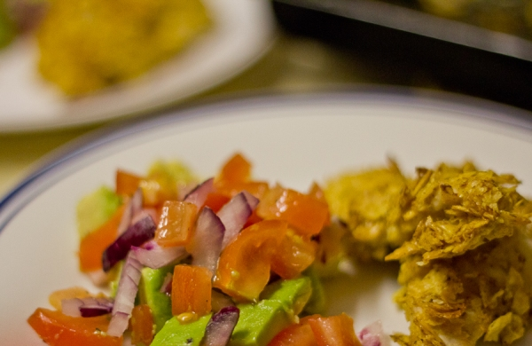 Tortilla chip crumbed chicken with an avocado, tomato and red onion salad