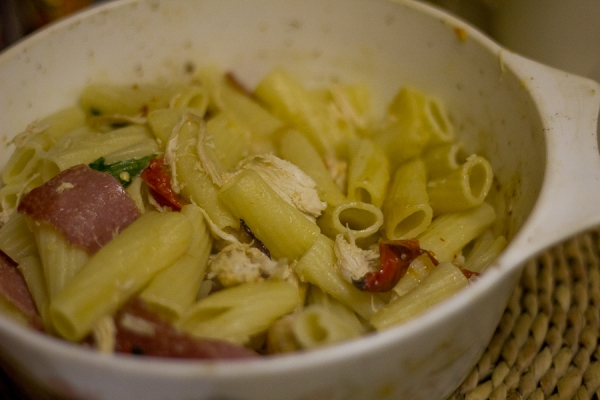 Rigatoni with salami, chicken, roasted red pepper and onion, in a casserole dish on a rattan mat